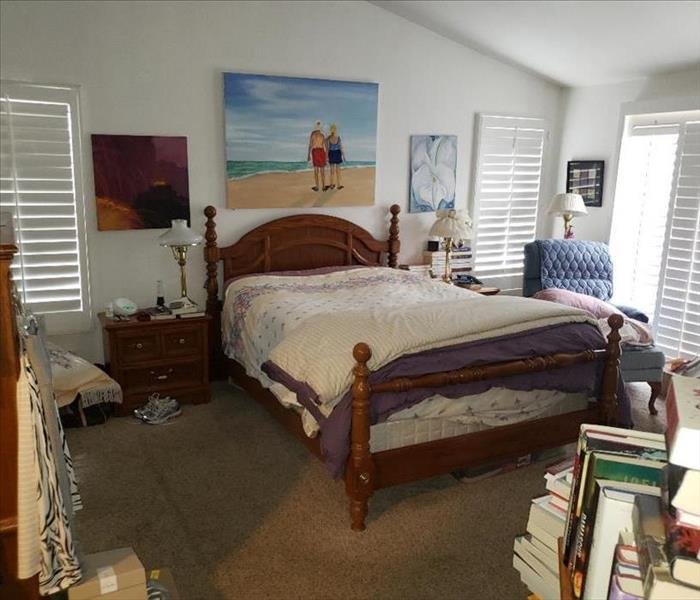 A furnished bedroom with a picture hanging on the wall. Books and knick-knacks around the room