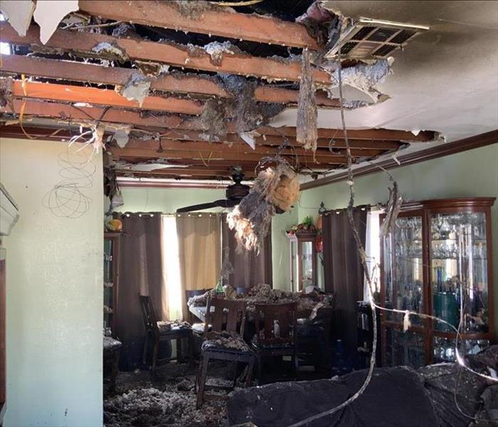 A living room with furniture filled with soot and fire damage. The ceiling drywall falling with insulation coming out of it.