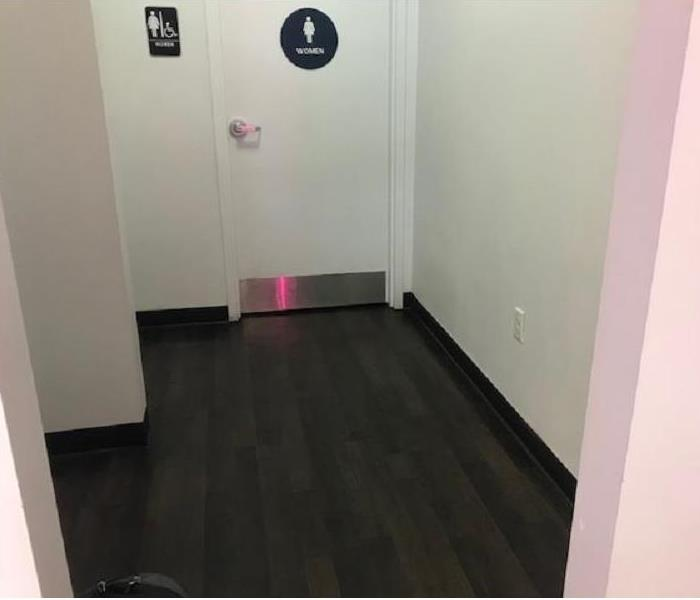 Wet Laminate floors in the hallway to the women's restroom.