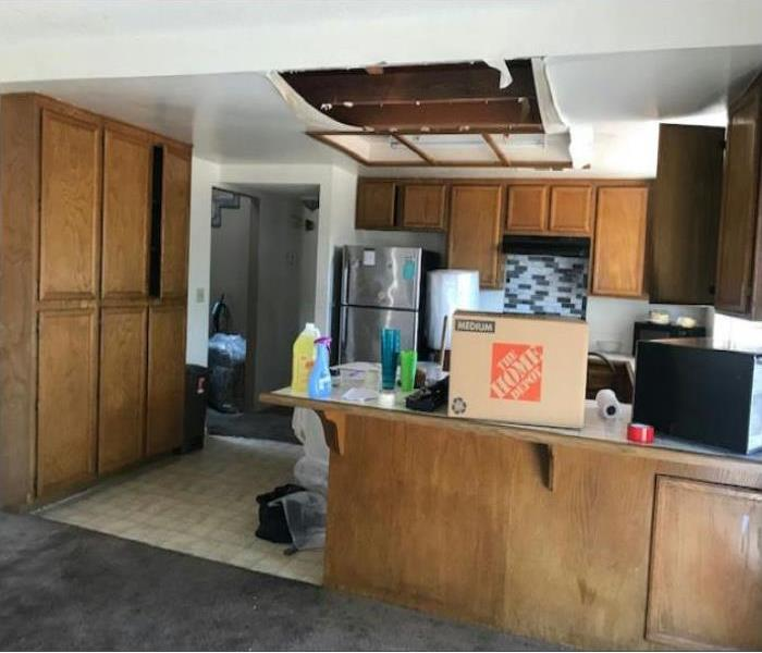A kitchen with brown cabinets and kitchen essentials. The ceiling in the kitchen has a open whole showing there was damage.