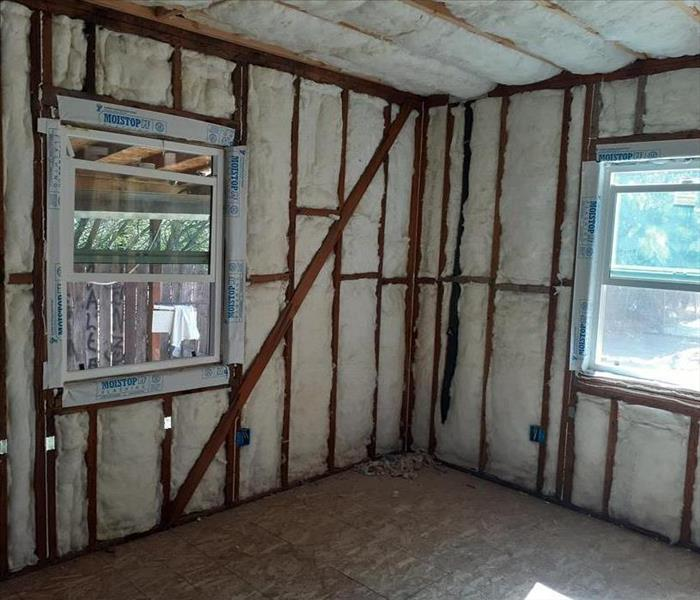 A open room with no drywall showing the insulation and framing.