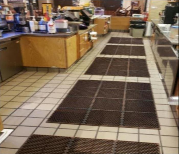 A restaurant kitchen nice and clean with brown rubber floor mats. Brown kitchen cabinets with kitchen essentials.