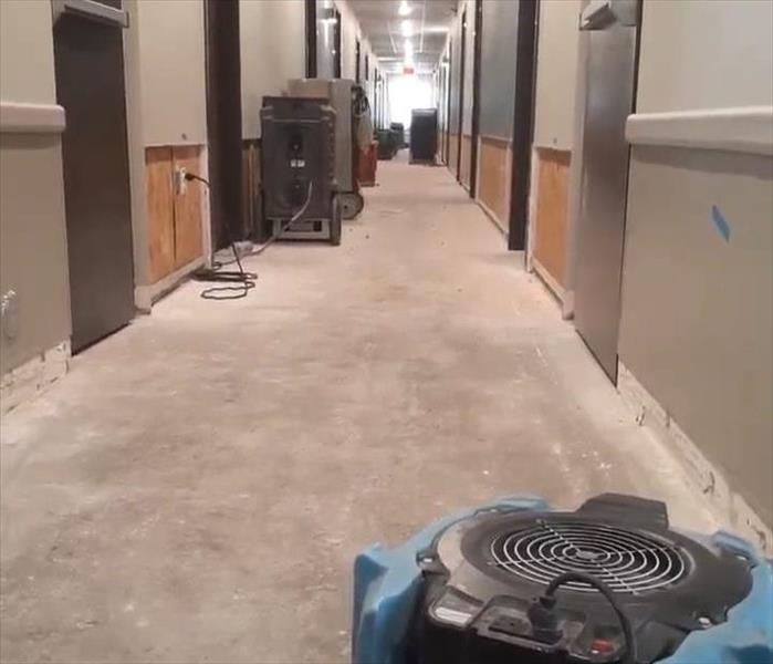 Air dryers sitting in the hallway of a hotel. Hallway has some drywall and floor missing.