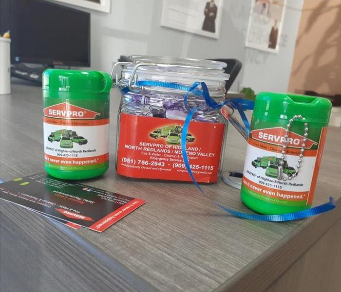 Candy jar, 2 green canisters and business cards on a office desk displaying our SERVPRO logo.