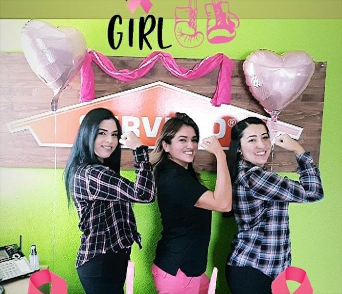 Our office girls flexing their right arm. Happy with balloons and pink banners surrounding them.